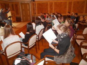 Chefdirigent Hans Richter unterweist die Chor-Workshopteilnehmer des Regentalgymnasiums im Schlosssaal.