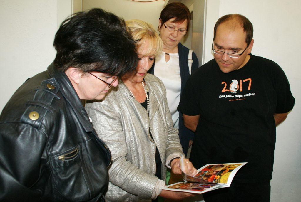 Blick in dem Ausstellungs-Folder (v. li.): Tanja Kraus, Beate Seifert, Dr. Lydia Mann und Pfarrer Gerhard Beck.