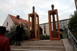 """Die Holzskulpturen """"Er"""" und """"Sie"""" bei der Pfarrkirche St. Josef."""