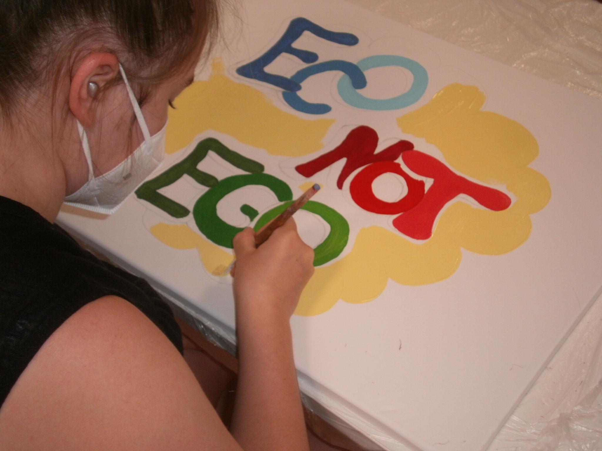 """Linda (14) zaubert das Motto """"ECO NOT EGO"""" im Graffiti-Style mit Pinsel und Acryfarben auf die Leinwand."""
